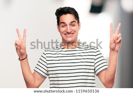 Young handsome tanned man with a proud, happy and confident expression; smiling and showing off success while gesturing victory with both hands, giving an