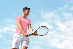 Young handsome tennis player with racket and ball prepares to serve at beginning of game or match. Beautiful colorful sports background, banner with copy space