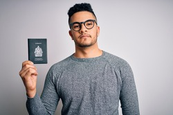 Young handsome tourist man on vacation wearing glasses holding Canada Canadian passport with a confident expression on smart face thinking serious