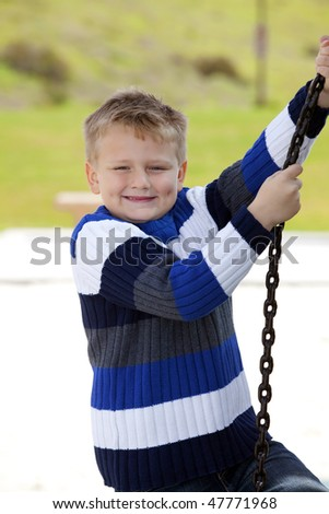 Young handsome 6 years old boy playing in the children's park