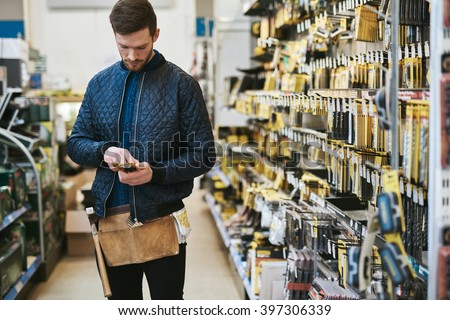 Young handyman checking information on his mobile before making a purchase in a hardware store