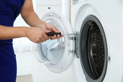 Young handyman fixing washing machine, closeup. Laundry day