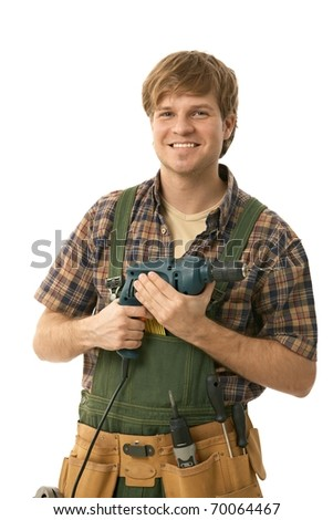 Young handyman holding power drill, smiling. Isolated on white.?