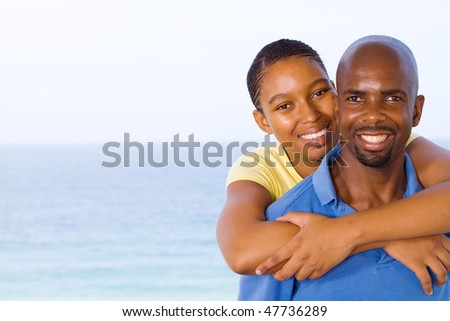 young happy african american couple piggyback, background is beautiful sea view