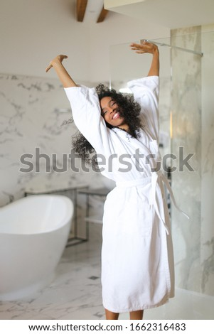 Young happy afro american woman wearing white bathrobe and dancing in hotel bathroom with marble walls. Concept of morning relax. Stock foto ©