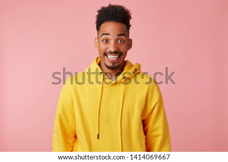 Young happy amazed african american guy in yellow hoodie, heard the news that his favorite band is coming to his city with a concert, broadly smiling and looking at the camera over pink background. Stockfoto ©