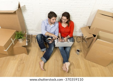young happy American couple sitting on floor moving in a new house or apartment flat using computer laptop choosing online furniture and household in real estate and independent lifestyle concept