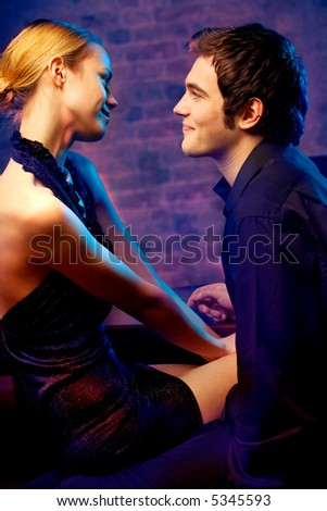 Young happy amorous attractive couple at night club