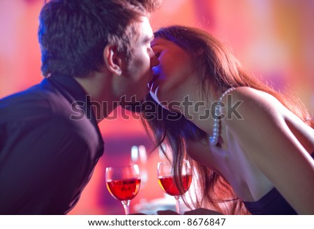 Young happy amorous couple kissing at restaurant