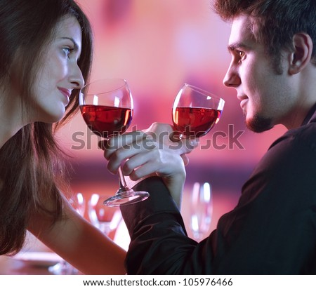 Young happy amorous couple with glasses of redwine on romantic date at restaurant