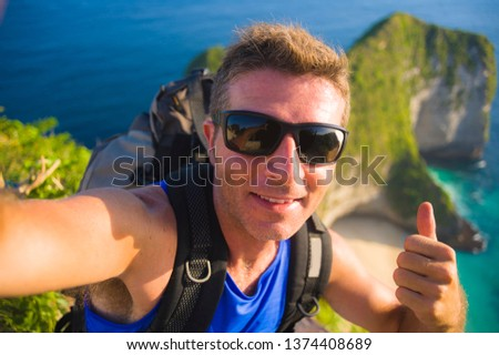 young happy and attractive backpacker man taking selfie portrait photo with mobile phone in front of amazing sea landscape smiling cheerful feeling free trekking on beautiful beach cliff