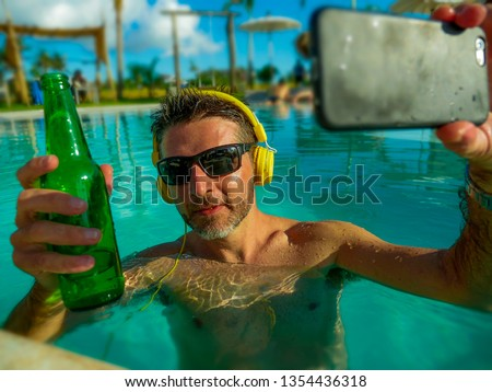 young happy and attractive man taking selfie picture with mobile phone drinking beer and listening to music at tropical resort swimming, pool enjoying Summer holidays relaxed and indulged