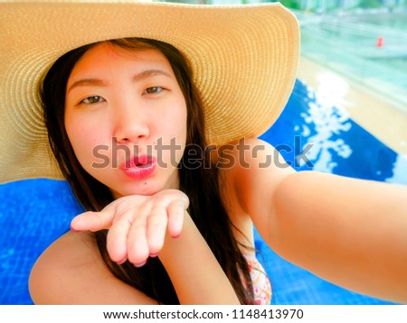 young happy and beautiful Asian Chinese tourist woman taking selfie picture with mobile phone camera at luxury hotel infinity pool with modern buildings urban background in travel holidays concept
