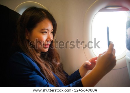 young happy and beautiful Asian Chinese woman traveling for business inside airplane cabin smiling cheerful using mobile phone taking selfie self portrait picture in air travel and tourism concept