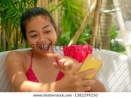 young happy and beautiful Asian Indonesian teenager girl in bikini sitting on pool bed with sarong taking selfie picture with mobile phone relaxed at tropical resort having fun
