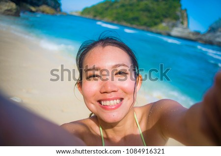 young happy and beautiful Asian Korean or Chinese tourist woman in bikini taking self portrait selfie photo with mobile phone at tropical paradise beach with white sand and turquoise sea water
