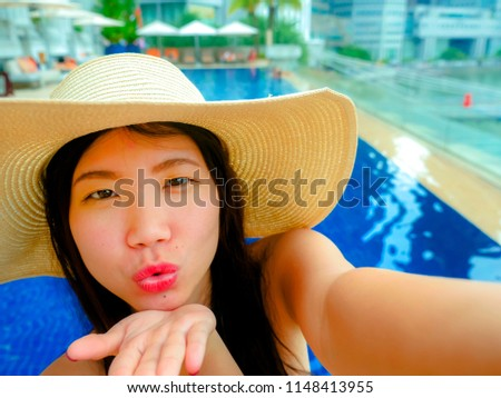 young happy and beautiful Asian Korean tourist woman taking selfie picture with mobile phone camera at luxury hotel infinity pool with modern buildings urban background in travel holidays concept