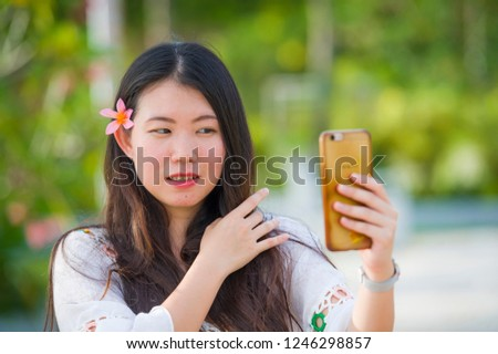 young happy and beautiful Asian Korean tourist woman taking selfie self portrait picture with mobile phone at tropical resort enjoying Summer holidays smiling posing with hair flower