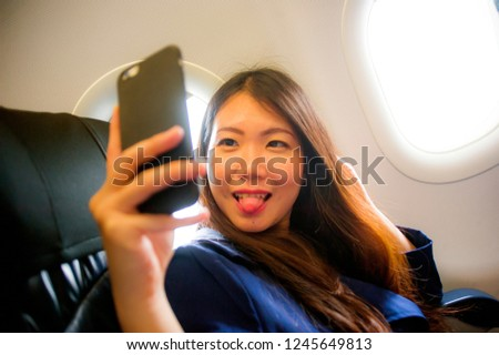 young happy and beautiful Asian Korean woman traveling for business inside airplane cabin smiling cheerful using mobile phone taking selfie self portrait picture in air travel and tourism concept