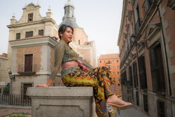 young happy and beautiful Asian woman wearing traditional Balinese kebaya dress - Indonesian girl in Bali clothes walking on street during holidays travel in Europe