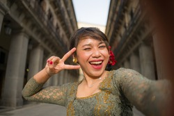 young happy and beautiful Asian woman wearing traditional Balinese kebaya dress taking selfie - Indonesian girl in Bali clothes walking on city street during holidays in Europe