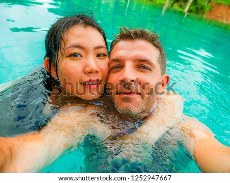 young happy and beautiful mixed ethnicity couple Asian woman and Caucasian man taking romantic selfie picture at tropical resort swimming pool enjoying honeymoon trip celebrating love