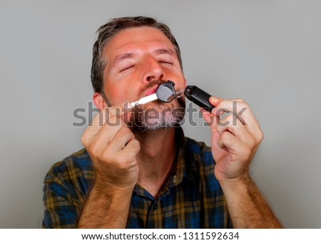 young happy and excited 30s or 40s attractive man kissing car key celebrating buying new automobile or motorbike isolated on grey background