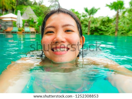 young happy and sweet Asian Chinese woman swimming in tropical resort pool taking selfie portrait picture with mobile phone smiling excited and cheerful enjoying holidays luxury tourist destination