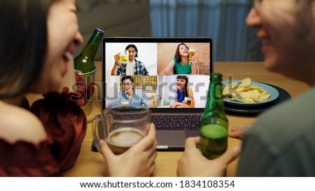 Young happy asian couple enjoy relax night party event online celebration festive with friends at home clinking beer with glass and bottle toasting drinking via video call.