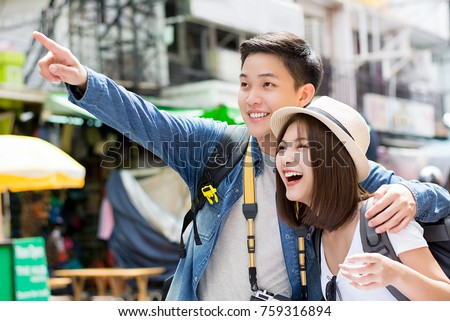Young happy Asian couple tourist backpackers enjoy visiting Khao San road on summer holiday traveling in Bangkok, Thailand
