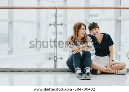 Young happy Asian girls best friends laugh and smile while sitting and having fun with smart phone mobile indoor.