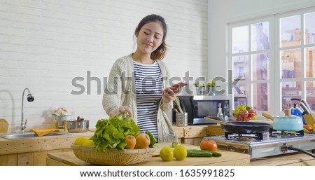 young happy asian japanese smiling woman wear sweater looking recipe in mobile phone while standing in kitchen. Vegetable salad dieting healthy lifestyle concept. girl cooking at home prepare food