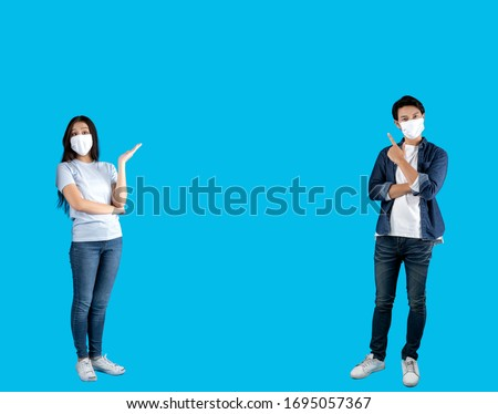 Young happy Asian man and woman pointing hands up to copy space wearing hygienic mask to prevent infection corona virus Air pollution pm2.5 and make social distance shoot on blue background
