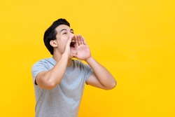 Young happy asian man announcing information with hands cup around mouth isolated on yellow studio background