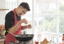 Young happy Asian man cooking ingredient in pan to make delicious food, Pour salt