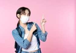 Young happy Asian woman pointing finger hands up to copy space wearing hygienic mask to prevent infection corona virus she jean jacket and carry backpack shirt shoot in isolated on pink background