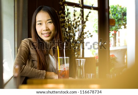 Young happy asian woman smiling and resting in the restaurant