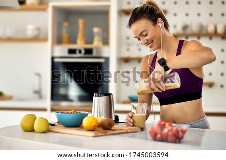Young happy athletic woman having a fruit smoothie for breakfast in the kitchen.  Stok fotoğraf ©