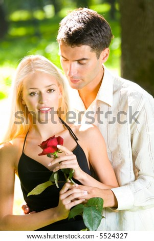 Young happy attractive couple with rose outdoors