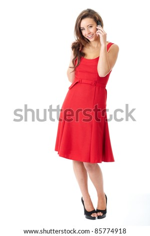 Young happy attractive female in red dress text using her mobile phone, shoot over white background