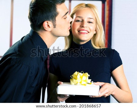 Young happy attractive happy smiling business people or couple with gift