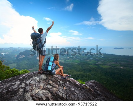 Young happy backpackers on top of a mountain enjoying valley view