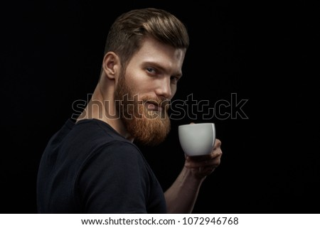 Young happy bearded man drinking morning fresh expresso coffee Caucasian handsome male business professional having coffee indoors close up studio portrait Side view portrait of stylish hairstyle man.