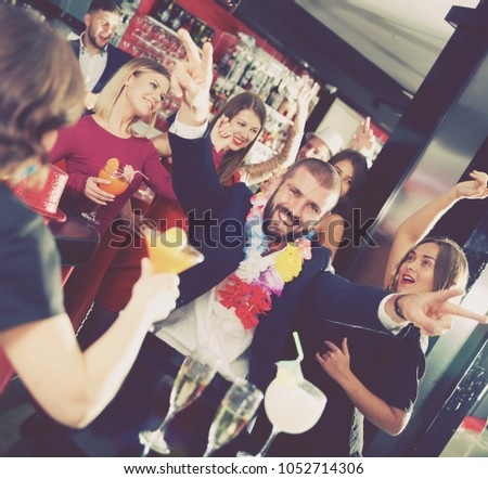 Young happy bearded man having fun on Hawaiian party at nightclub #1052714306