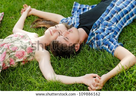 Young happy beautiful couple man and woman lying outdoors on the bright sunny day on green lawn and looking up