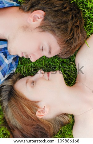 Young happy beautiful couple man and woman lying outdoors on the bright sunny day on green lawn and looking at each other head shot