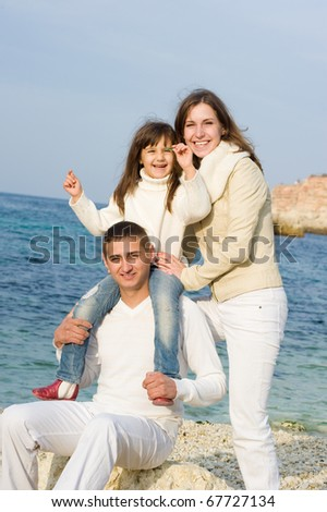 Young happy beautiful family at sea