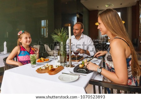Young happy beautiful smiling Caucasian family of father, mother and daughter enjoying dinner together by served restaurant table. Holiday celebration at resort's hotel #1070523893