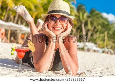 young happy beautiful woman enjoying summer vacation on tropical sand beach, sunbathing, outdoor portrait