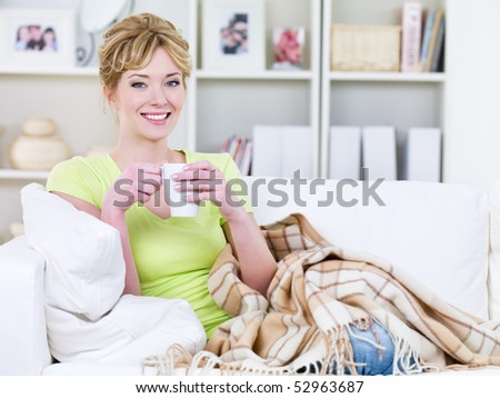Young happy beautiful woman with cup of warming beverage at home